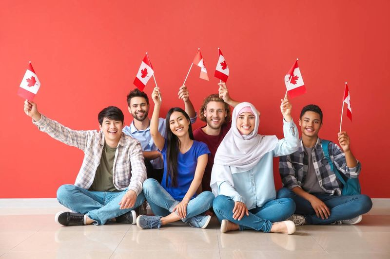 multi-ethnic people holding Canadian flags | immigrate in Canada