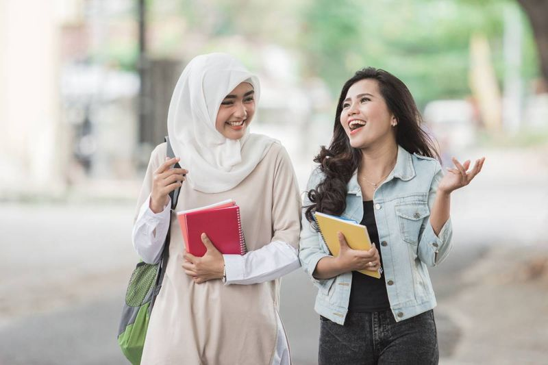 Female Muslim and Asian students smiling
