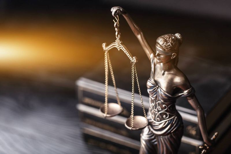 scales of justice on desk in front of law books | immigrate to Canada