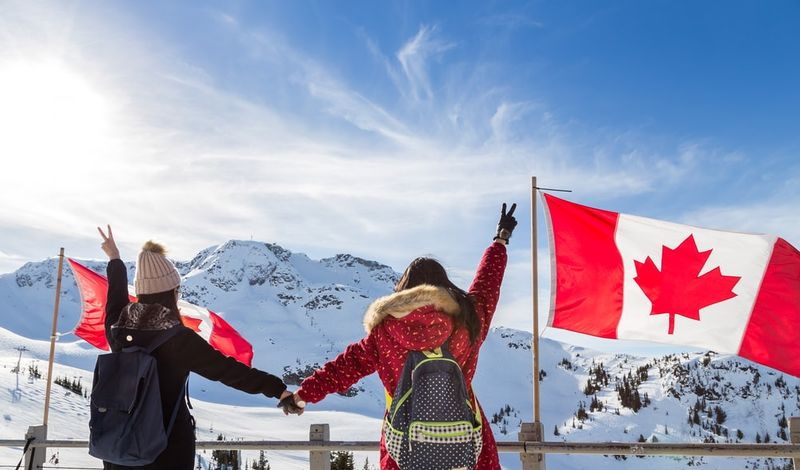 Canadian girls with their hands in the air at whistler on a snow-covered mountains with the Canadian flag blowing