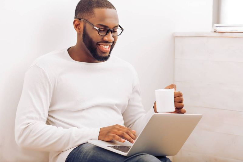smiling African American man applying for visa on laptop drinking coffee | immigrate to Canada