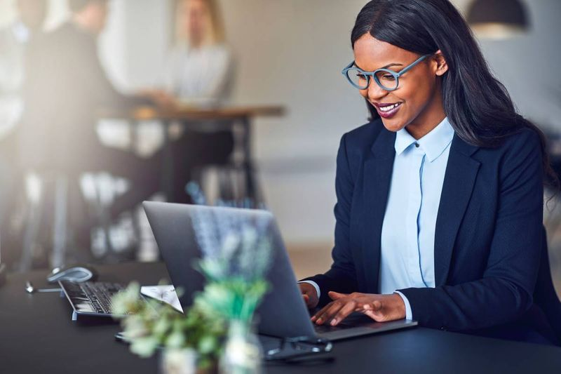 smiling-african-american-business-woman-typing-on-laptop   Express Entry Canada