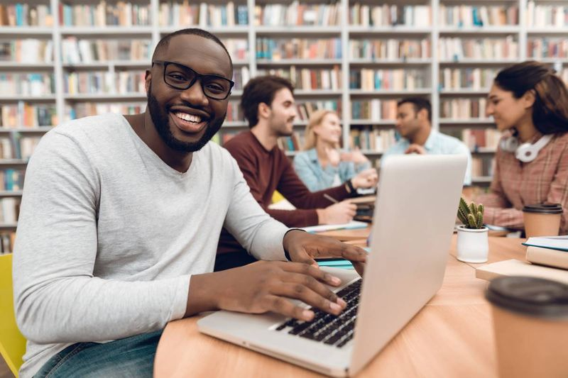 smiling African student in university library working on laptop |  study in Canada