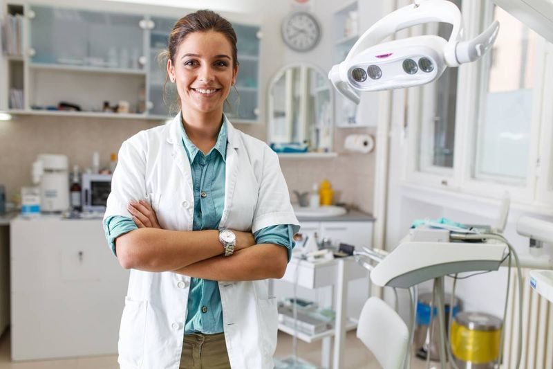 smiling-female-dentist-standing-in-office   Express Entry Canada