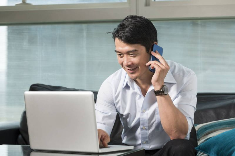 smiling handsome Asian man talking on phone and working on laptop   real-or-fake