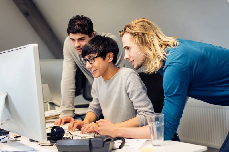 tech worker at desk with colleagues in office | immigrate to Canada