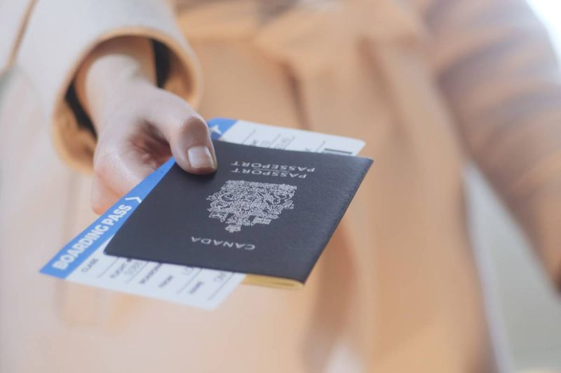 woman holding passport and plane ticket   immigrate to Canada