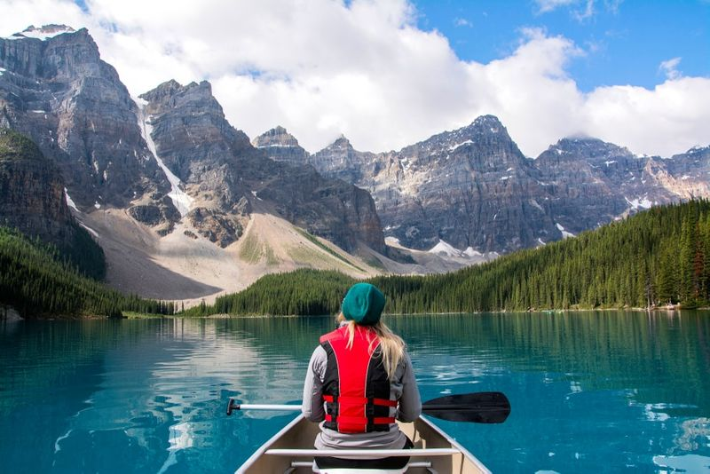 woman in boat moraine lake alberta canada enjoying the quality of life | live and work in Canada