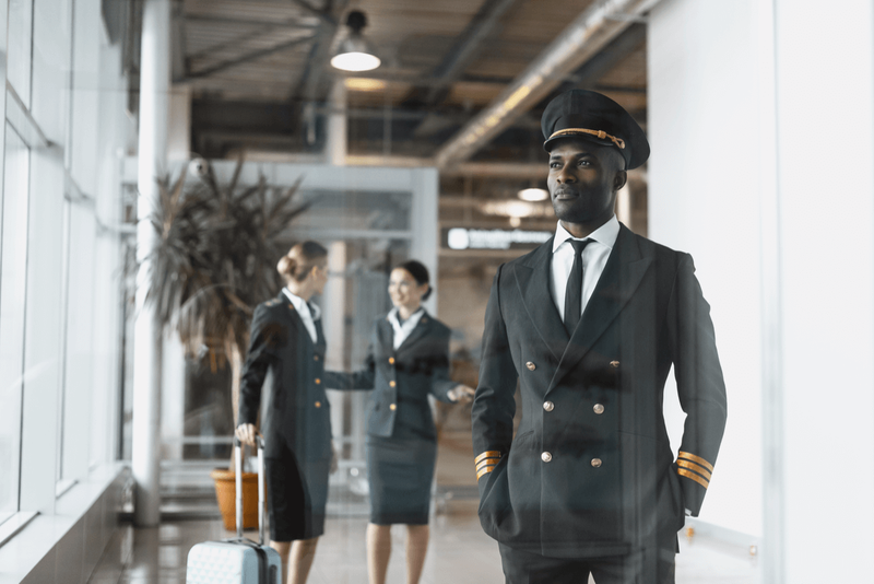 young pilot standing with hostesses