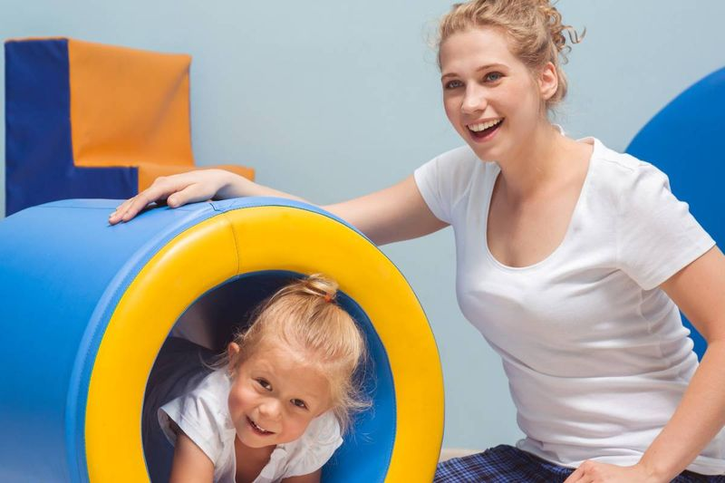 young occupational therapist helping child exercise | move to Canada